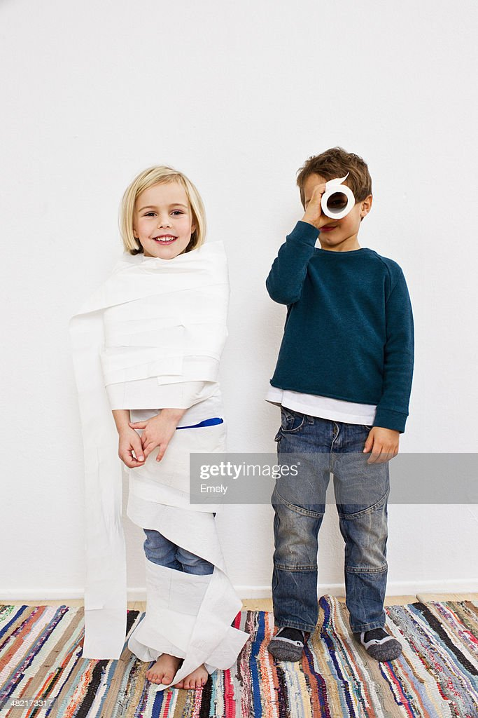 Studio shot of sister and brother with toilet rolls