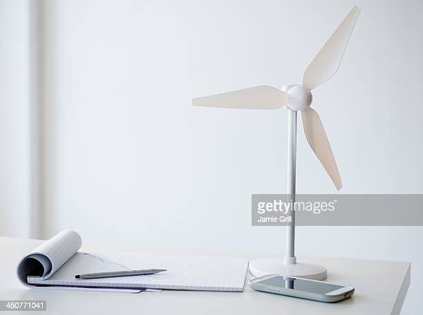 Studio Shot of small wind turbine, mobile phone and note pad on desk
