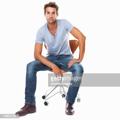 Studio shot of smart young man sitting on chair