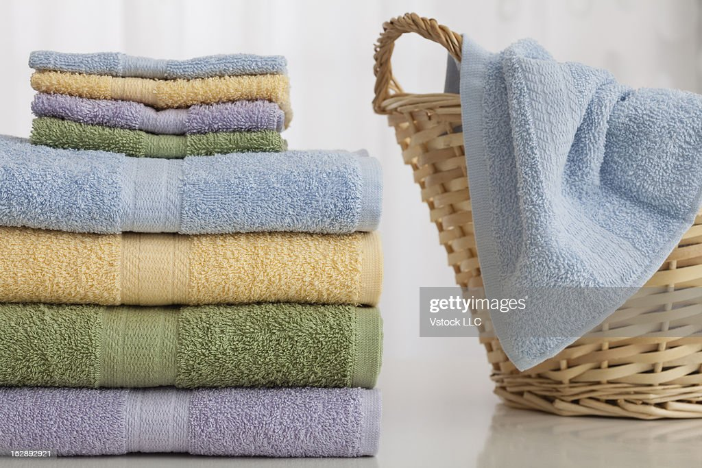 Studio shot of stack of pastel colored towels with Wicker Basket