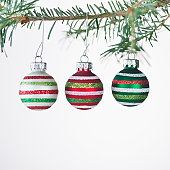 Studio shot of striped Christmas ornaments hanging on Christmas tree