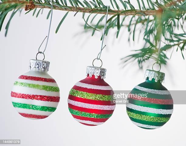 Studio shot of striped Christmas ornaments hanging on Christmas tree