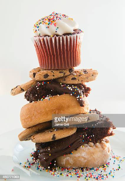Studio Shot of tower made of cookies, brownie, donuts with cupcake on top