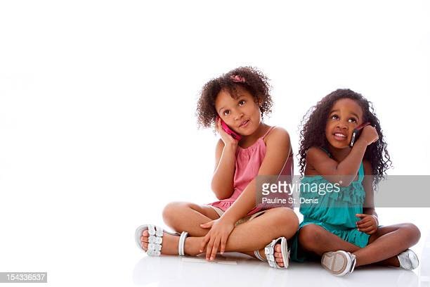 Studio shot of two girls (2-5, 6-7) sitting and talking on mobile phones