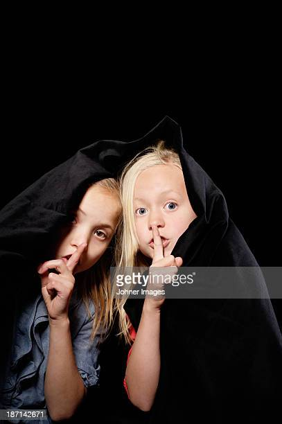 Studio shot of two girls with fingers on lips
