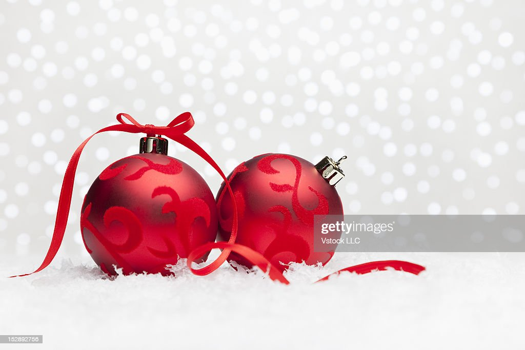 Studio shot of two red christmas baubles on fake snow