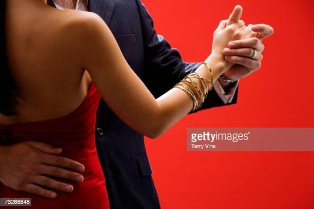 Studio shot of well dressed couple dancing