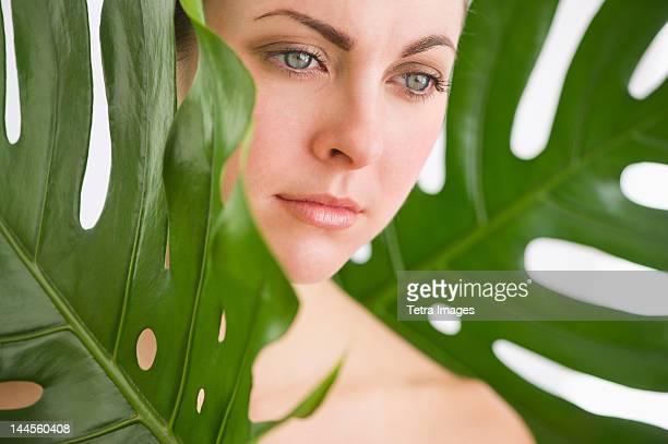 Studio shot of woman between leaves