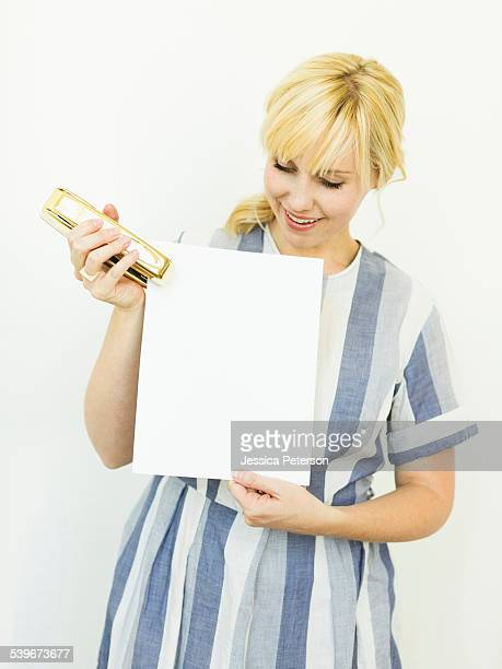 Studio shot of woman holding blank paper and stapler