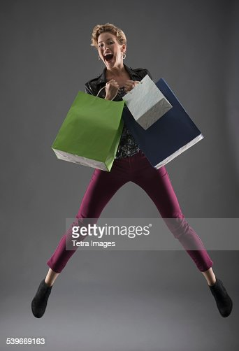 Studio shot of woman jumping with shopping bags