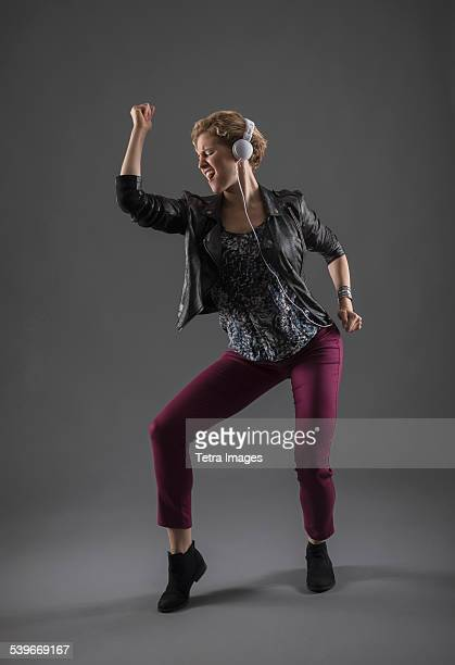 Studio shot of woman listening to music and dancing