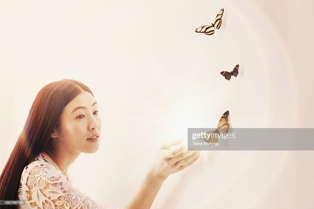 Studio shot of woman looking at butterflies
