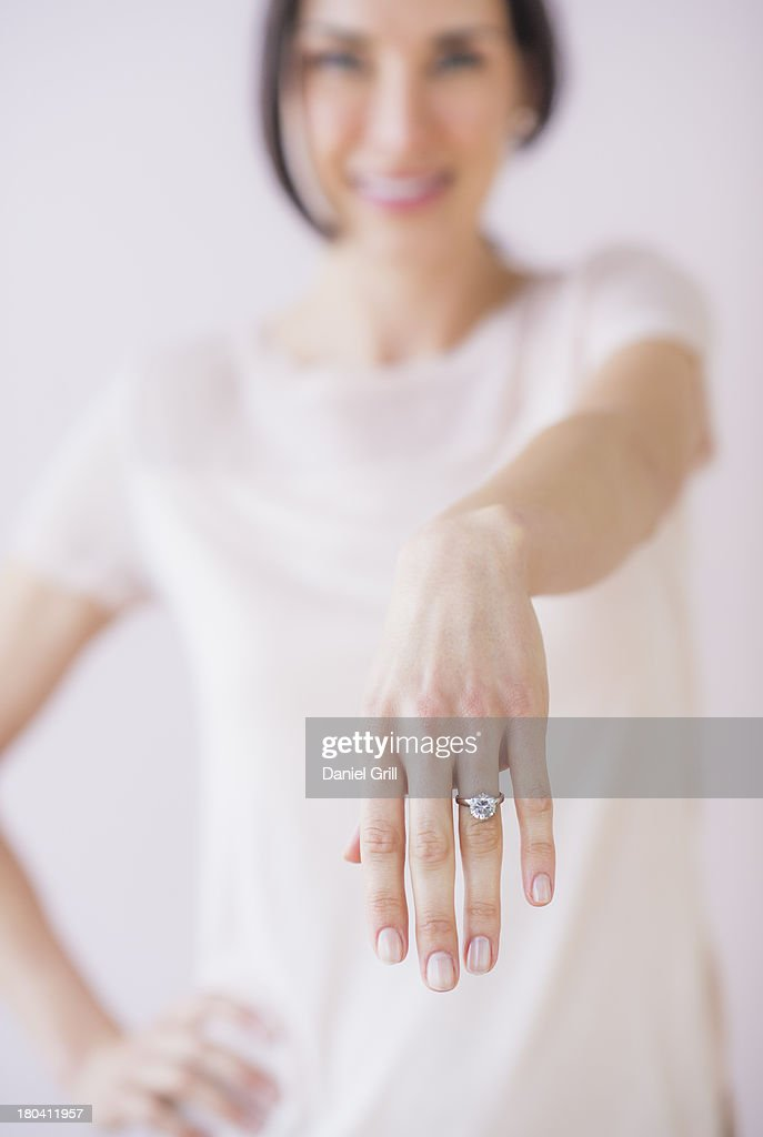 Studio Shot of woman showing her engagement ring