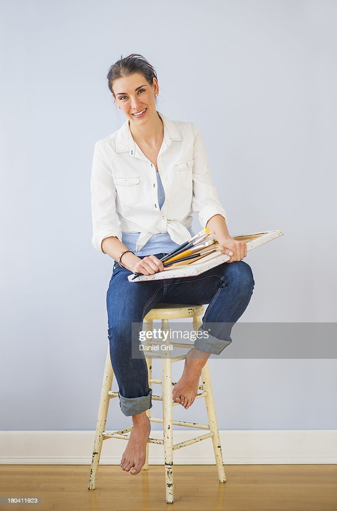 Studio Shot of woman sitting on stool, holding paintbrushes and artist's canvas