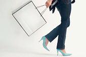 Studio shot of woman walking with shopping bag