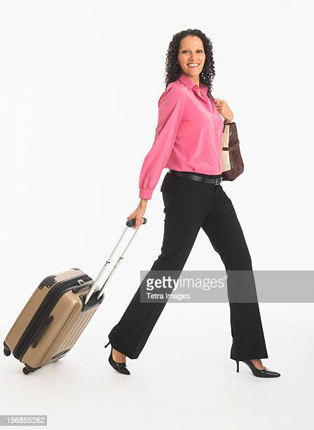 Studio shot of woman walking with suitcase