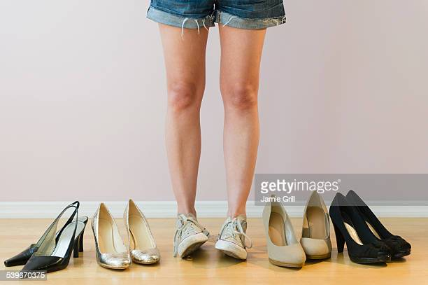 Studio shot of woman with pairs of shoes