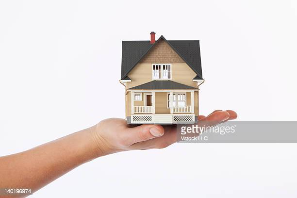 Studio shot of woman's hand holding model house