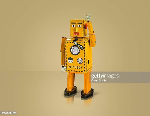 Studio shot of yellow robot with arm raised
