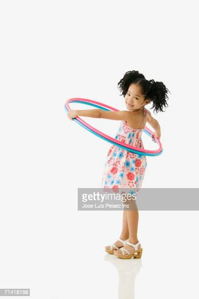 Studio shot of young African girl playing with hula hoops