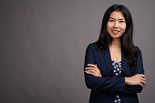 Studio shot of young Asian businesswoman against gray background horizontal shot