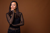Studio shot of young Asian woman wearing black long sleeved shirt with sheer fabric against colored background horizontal shot