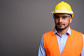 Studio shot of young bearded Persian man construction worker against gray background