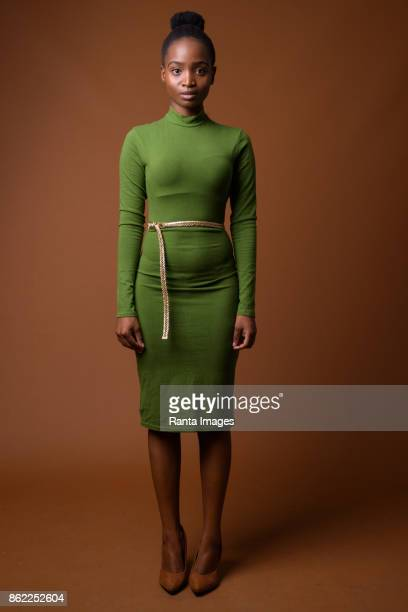 Studio shot of young beautiful African Zulu businesswoman wearing green outfit against colored background