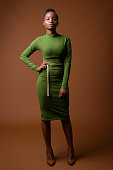 Studio shot of young beautiful African Zulu businesswoman wearing green outfit against colored background colored background vertical shot