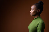 Studio shot of young beautiful African Zulu businesswoman wearing green outfit against colored background colored background horizontal shot