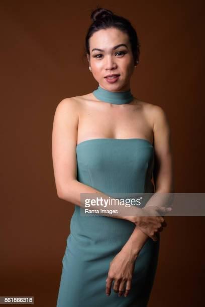 Studioaufnahme von jungen schönen asiatischen Transgender-Frau trägt blaue Kleid vor farbigem Hintergrund