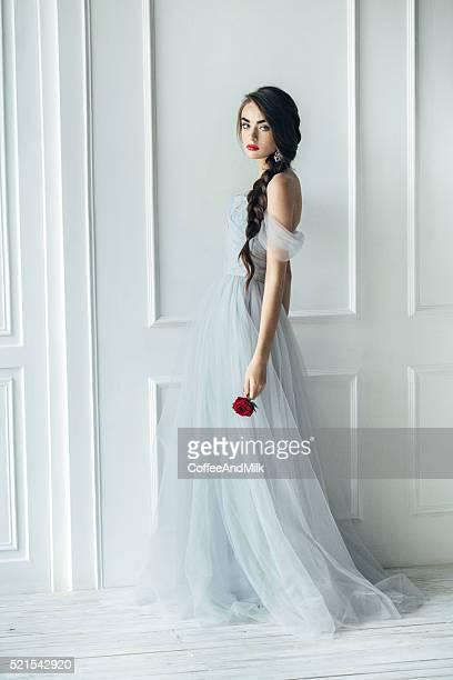 Studio shot of young beautiful bride with big rose