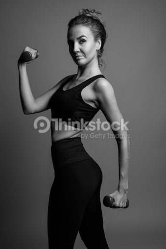 6ec8406e49 Studio shot of young beautiful woman ready for gym against gray background  in black and white