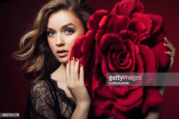 Studio shot of young beautiful woman with big rose