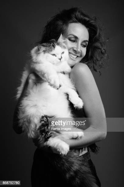 Studio shot of young beautiful woman with curly hair holding cute cat against gray background