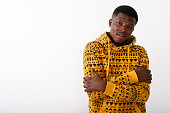 Studio shot of young black African man feeling cold against white background horizontal shot