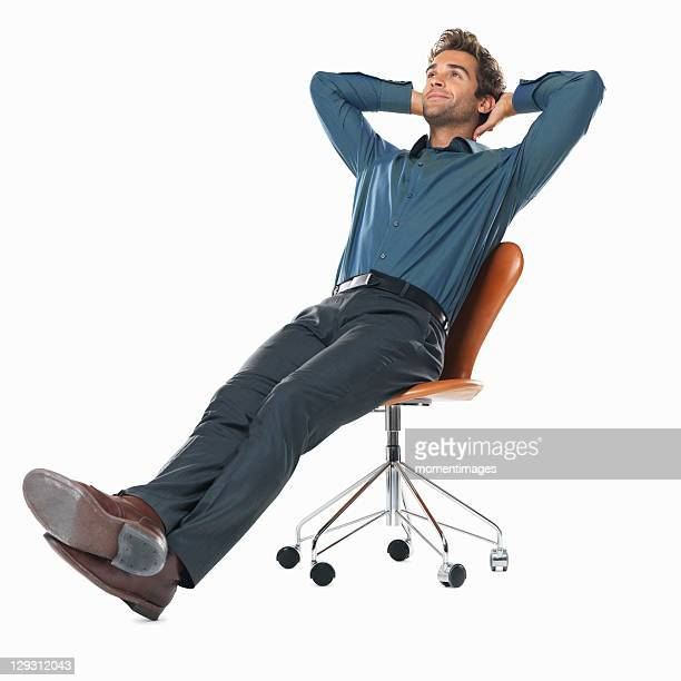 Studio shot of young business man relaxing on chair with hands behind head