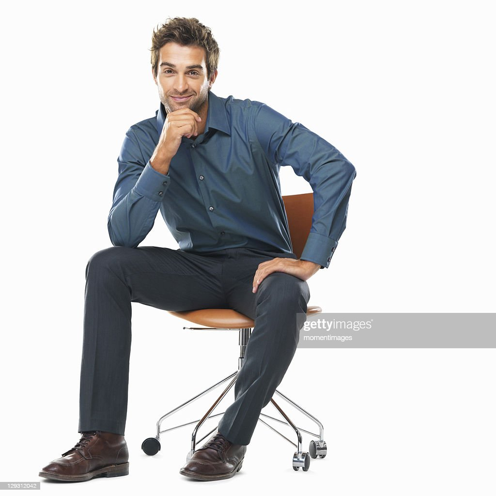 Studio shot of young business man sitting on chair with hand on chin and smiling