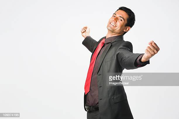 Studio shot of young businessman with arms raised in celebration