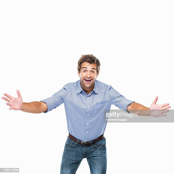 Studio shot of young cheerful man with arms outstretched
