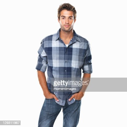 Studio shot of young confident man with hands in pockets
