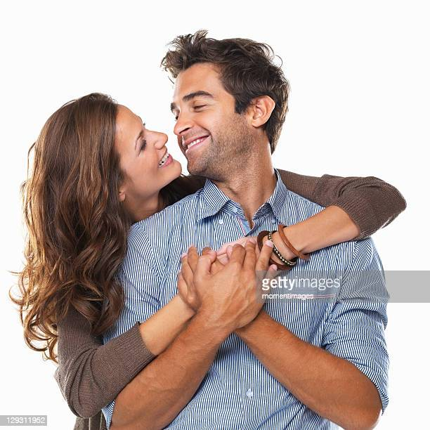 Studio shot of young couple smiling and looking at each other