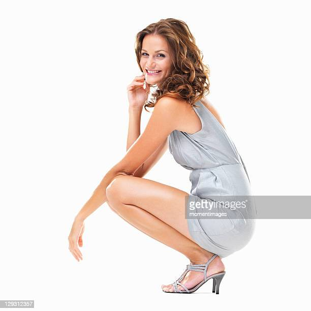 Studio shot of young elegant woman in crouched position