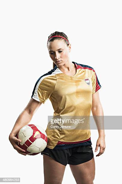 Studio shot of young female soccer player holding ball