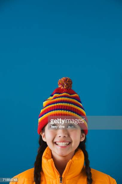 Studio shot of young girl wearing hat and jacket