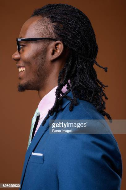Studio shot of young handsome African businessman wearing blue suit and eyeglasses against colored background