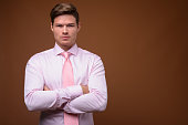 Studio shot of young handsome businessman wearing pink shirt with pink necktie against colored background horizontal shot
