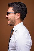 Studio shot of young handsome Hispanic businessman against colored background vertical shot