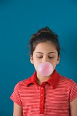 Studio shot of young Hispanic girl blowing bubble gum