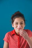 Studio shot of young Hispanic girl with popped bubble gum bubble